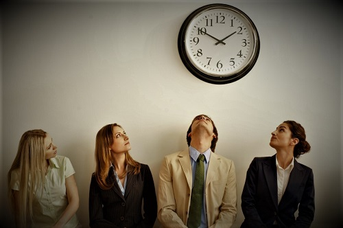 Four businesspersons sitting on bench looking up at clock. Horizontally framed shot.